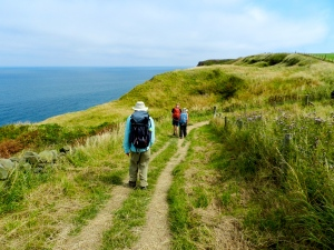 Walking the last miles of the England Coast to Coast Walk approaching Robin Hood's Bay on the North Sea
